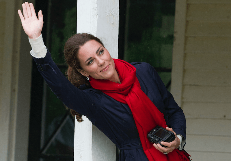 Kate Middleton with her camera around her neck waving outside