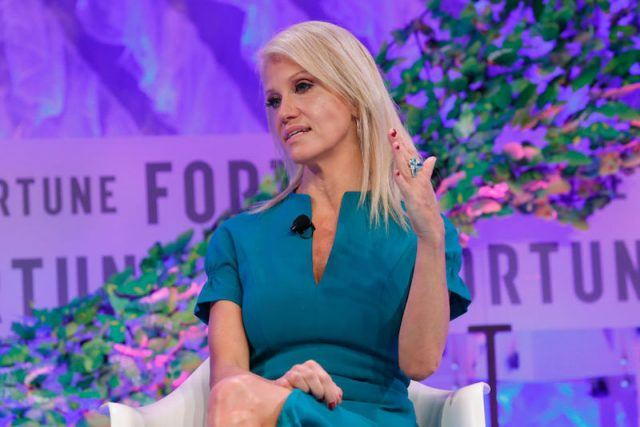 Kellyanne Conway sits on a white couch in a blue dress.