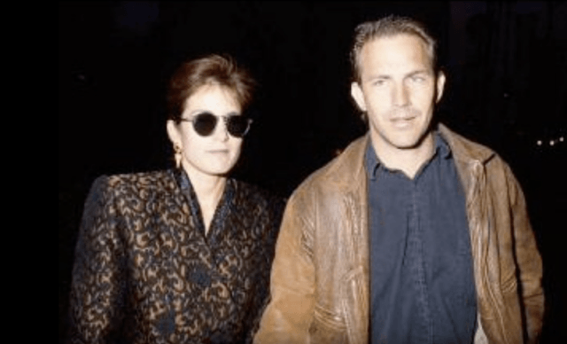 Cindy Silva and Kevin Costner walking alongside each other down a dark street.