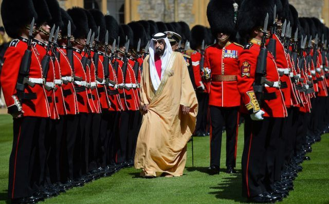 Sheikh Khalifa bin Zayed Al Nahyan walks past a row of armed guards.