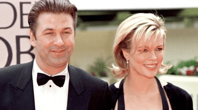 Alec Baldwin and Kim Basinger posing for photographers on a red carpet.