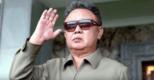 King Jung Il waving at a crowd while wearing sunglasses.