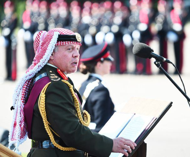King Abdullah II of Jordan stands in front of a podium while wearing a uniform.