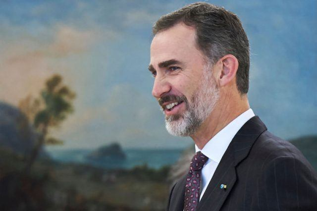 King Felipe Of Spain smiles while standing in front of a painting.