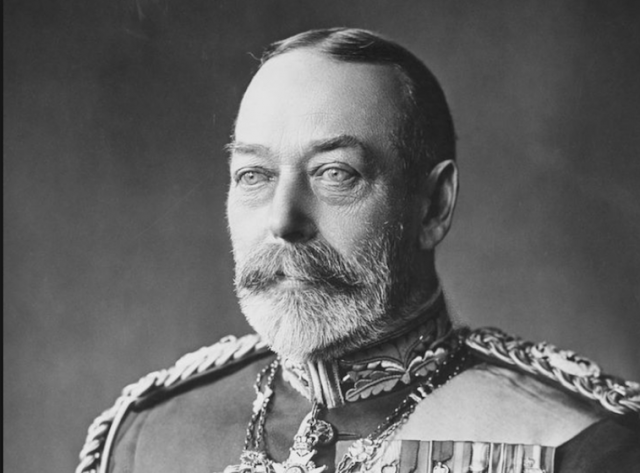 King George V stands in front of a wall in a decorated uniform.