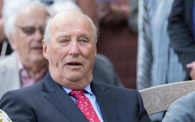 King Harald of Norway watches a presentation while sitting in an audience.