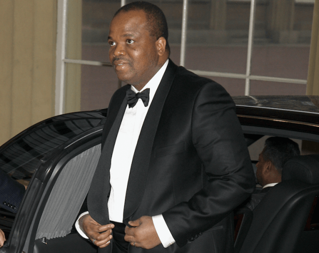 King Mswati III emerges from a black car wearing a tuxedo and tie.