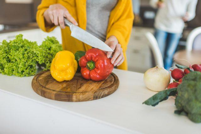 A person chops up bell peppers on a cutting board.