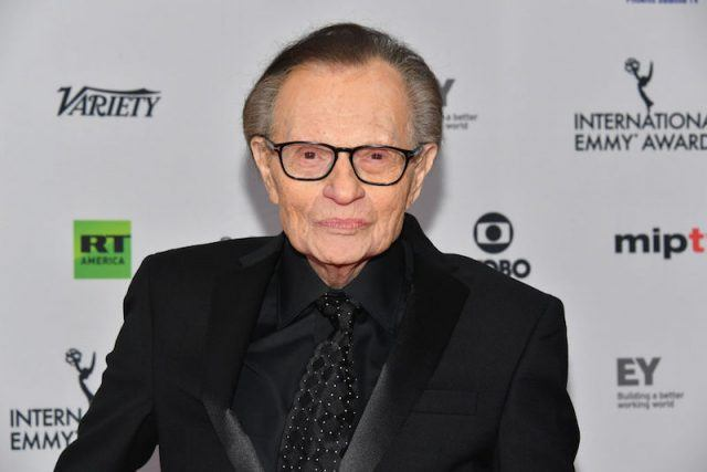 Larry King wearing a black suit and glasses on a red carpet.