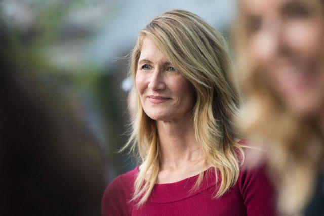 Laura Dern standing among a group of people at an event.