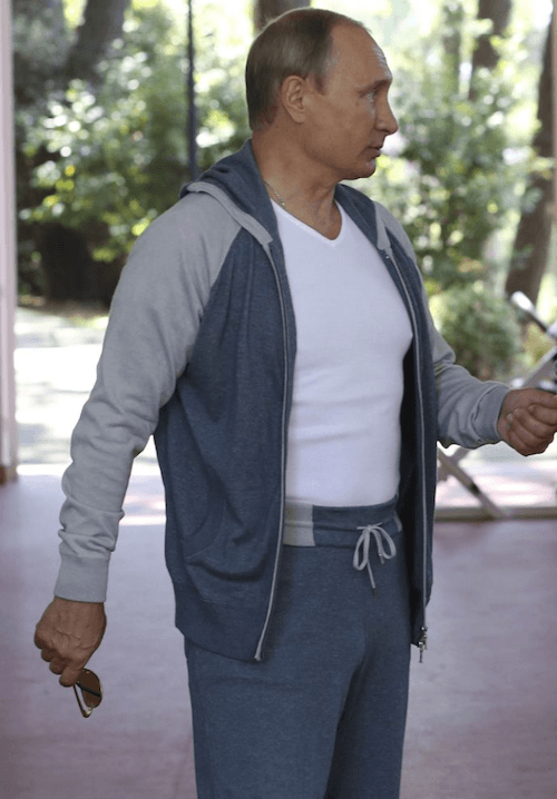 Putin walks while wearing a white and grey workout outfit.