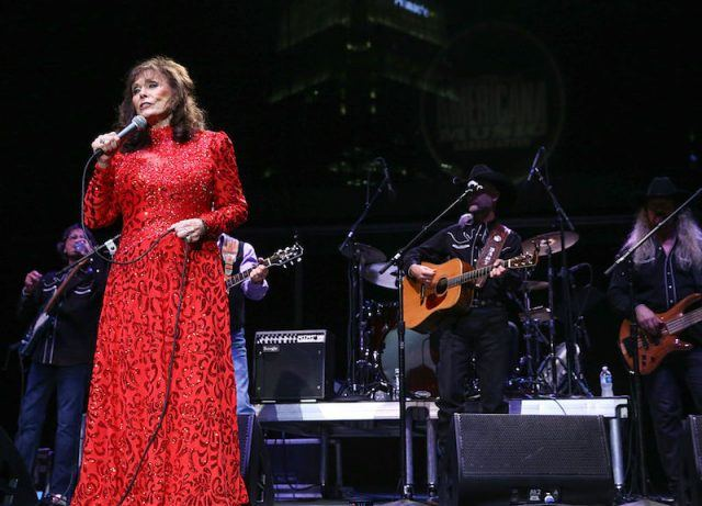 Loretta Lynn performing in a red dress.