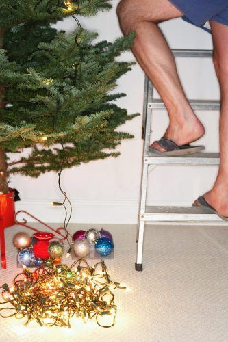 Man on stepladder decorating Christmas tree