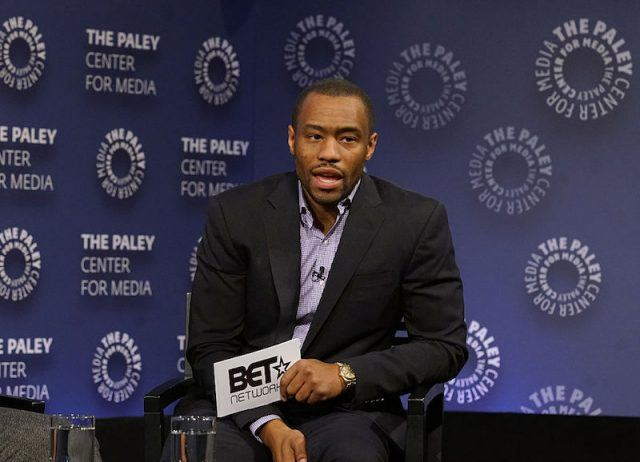 Marc Lamont Hill sits holding a notecard during an interview.