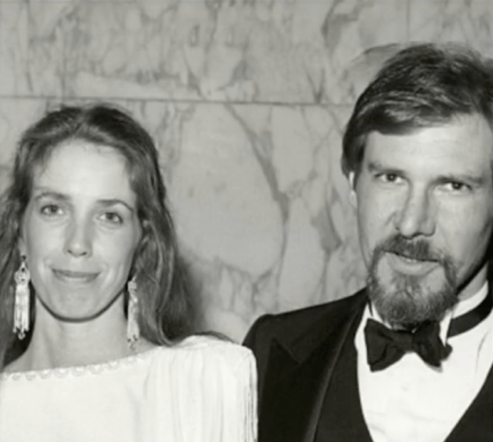 Mary Marquardt and Harrison Ford posing in front of a marble wall.
