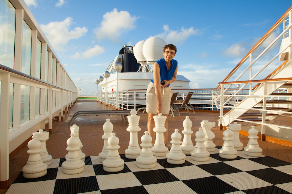 A mature, smiling woman prepares to move a large chess piece on a cruise ship