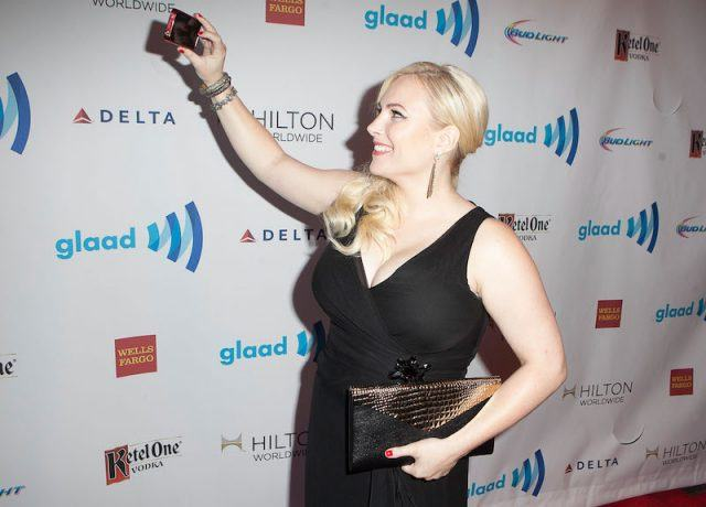 Meghan McCain taking a selfie on a red carpet while wearing a black dress and holding a clutch.