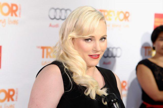 Meghan McCain posing for photographers at a red carpet in a black gown.