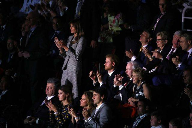 Melania Trump standing while she applauds in an audience.