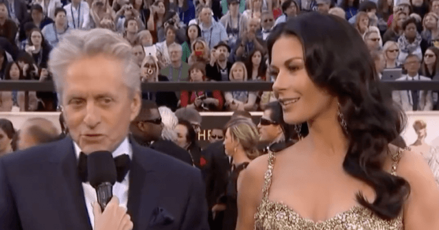 Michael Douglas and Catherine Zeta-Jones being interviewed on a red carpet.