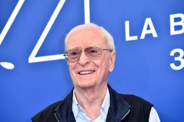 Michael Caine smiles while posing in front of a blue backdrop.