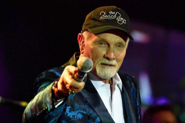 Mike Love stands on stage pointing a microphone at the audience.