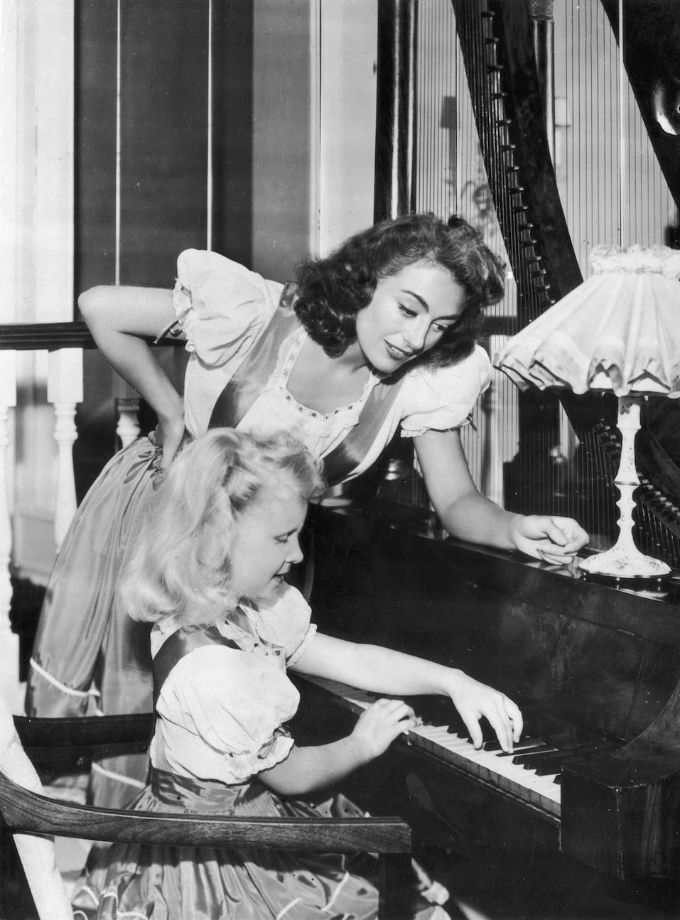 Hollywood actress Joan Crawford supervises her adoptive daughter Christina's piano practice