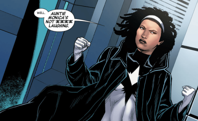 Monica Rambeau stands in a black cloak in front of a building.