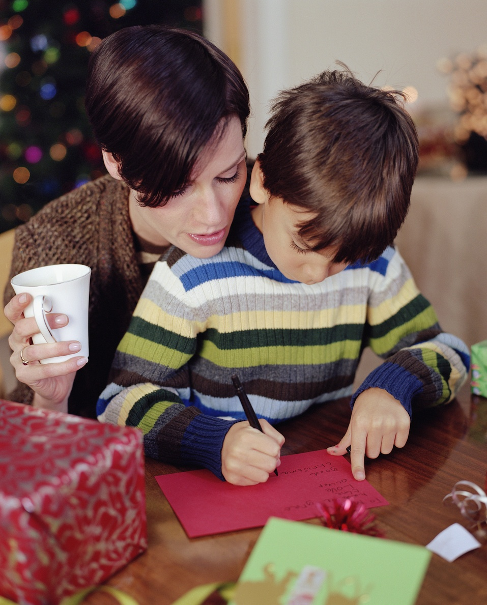 Mother helping son (6-8) write christmas card