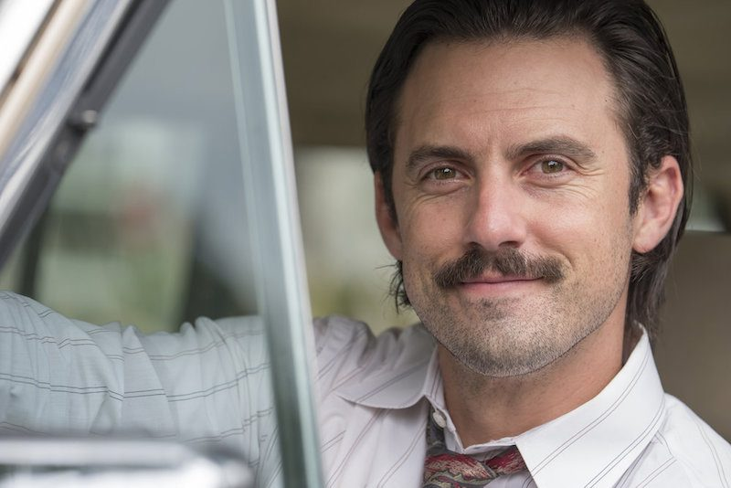 Milo Ventimiglia as Jack sits in the drivers seat of a car and smiles
