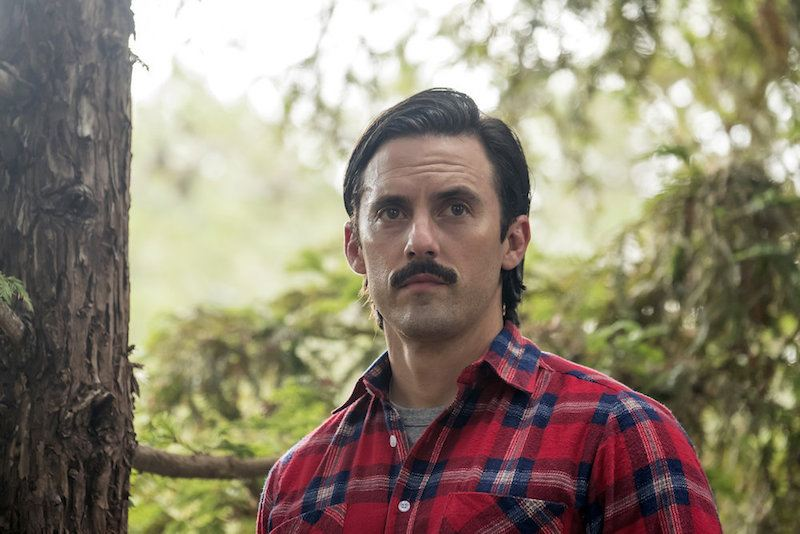 Milo Ventimiglia as Jack stands in a red plaid shirt
