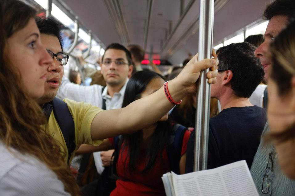 People ride the New York City subway into Manhattan during the morning commute