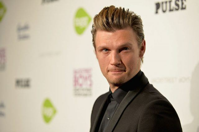 Nick Carter looking towards photographers while posing on a red carpet.
