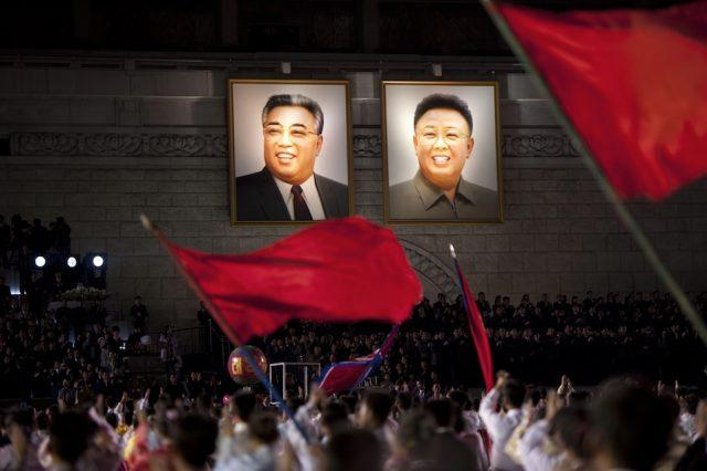 North Koreans wave flags in front of portraits of North Korean late president Kim Il-Sung (L) and his son Kim Jung-Il during celebrations