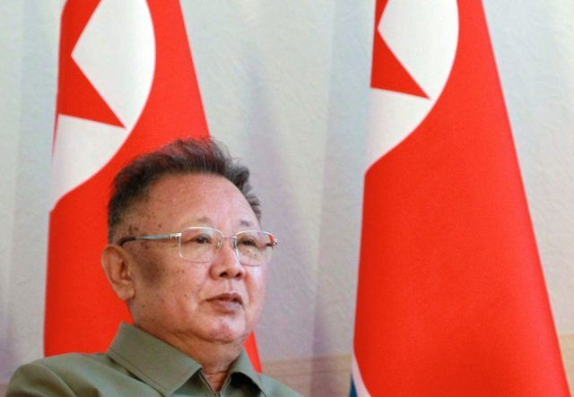 Kim Jong Il standing in front of a couple of flags.