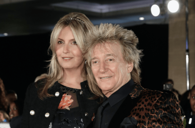 Rod Stewart and Penny Lancaster smile together while standing closely for a photo.