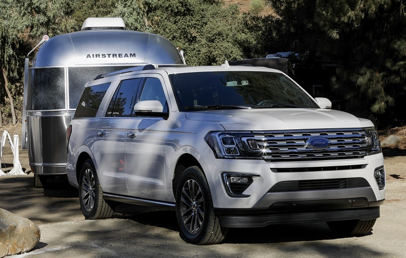 Shot of white 2018 Ford Expedition towing trailer
