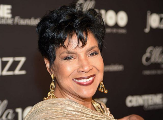 Phylicia Rashad smiles while wearing a gold dress and earrings.