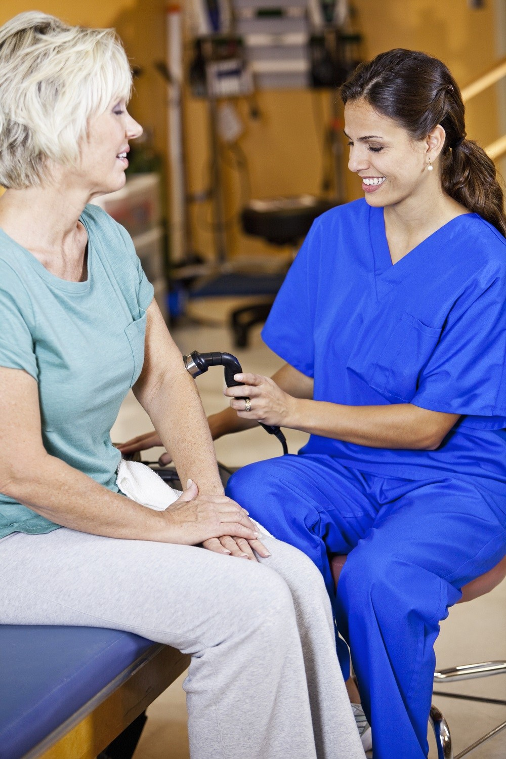 Physical therapist massaging a patient using device