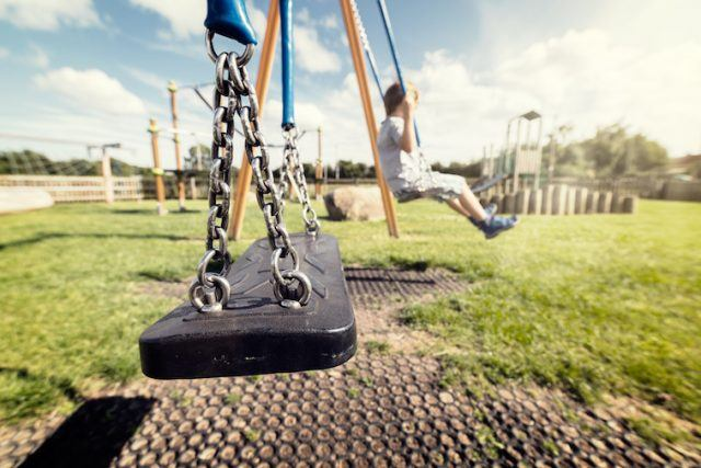 A child sits on a playground swing.