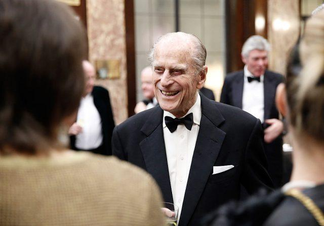 Prince Charles laughs while networking with guests.