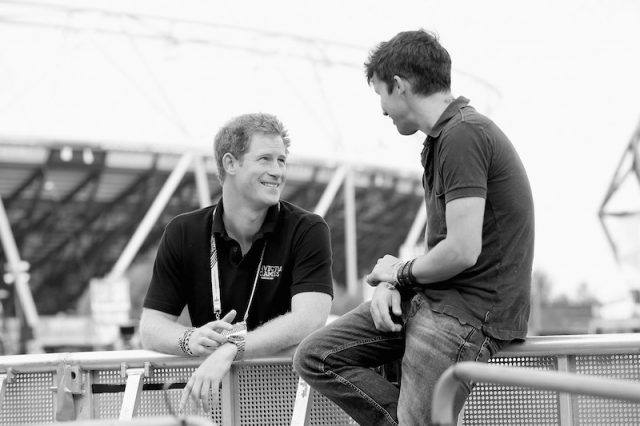 Prince Harry talking to James Blunt on stage.