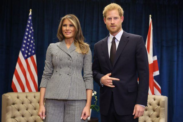 Prince Harry standing with Melania Trump on stage.
