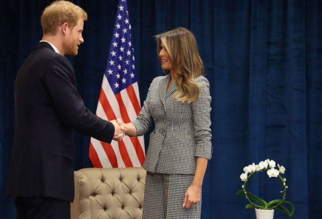 Melania shaking hands with Prince Harry on stage.