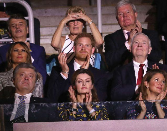 Prince Harry sitting in an audience applauding as he looks onward.