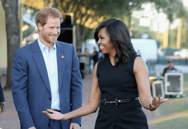 Prince Harry and Michelle Obama smiling together as they talk outside.