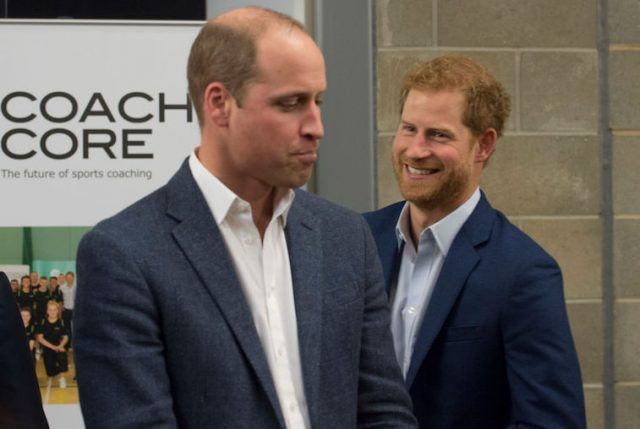 Prince William and Prince Harry standing next to each other as they smile and laugh.