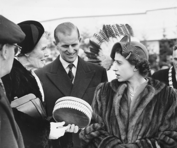 Prince Phillip stands with Princess Elizabeth while chatting with two people outdoors.