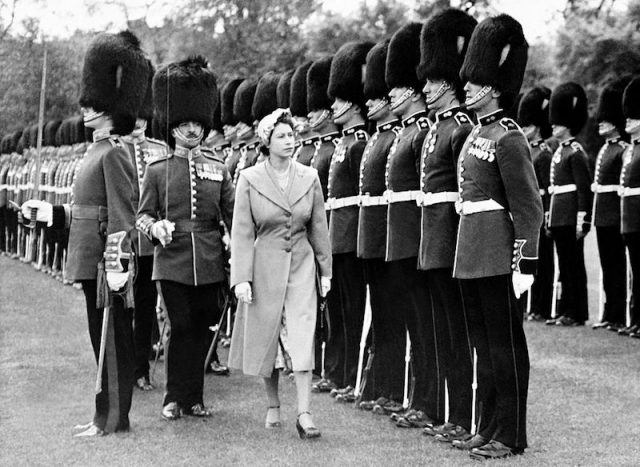 Queen Elizabeth walks past a group of guards.