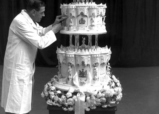 A baker adds details to the wedding cake.
